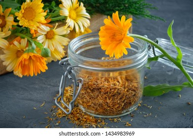 Healthy marigold flowers. Medicinal herbs in wooden crate and glass jar of dry calendula petals.
