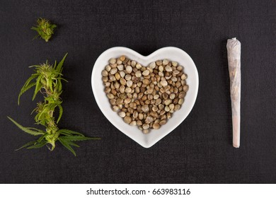Healthy Marijuana medicine. Buds, seeds in heart shaped bowl and cannabis joint from above on black background. I love alternative medicine.