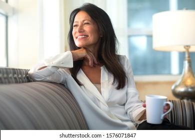 Healthy mature hispanic woman sitting on a sofa.