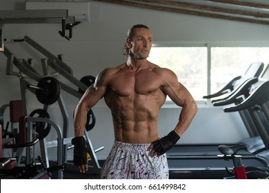Healthy Mature Tattoo Man Standing Strong In The Gym And Flexing Muscles - Muscular Athletic Bodybuilder Fitness Model Posing After Exercises