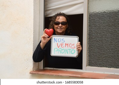 Healthy Mature Woman in isolation during COVID-19 Pandemic at window holding up red heart and sign in Spanish Language (Nos Vemos Pronto) We will see each other soon.