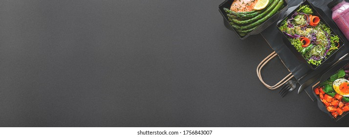 Healthy meal diet plan daily ready menu black background, fresh dishes in paper boxes, smoothie, fork knife on paper eco bag as food delivery service at home in office, flat lay, website photo banner.