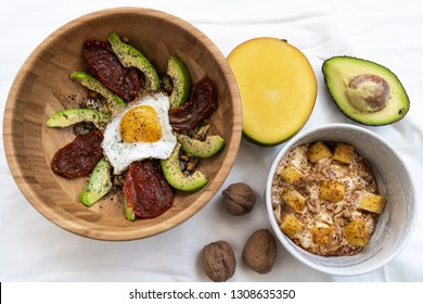 Healthy meal made of egg over avocado slices and dry tomatos and a bowl of yogurt, mango, chestnuts and coffee powder as dessert