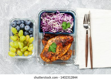 Healthy meal prep container with  chicken and cole slaw. Container with berries. Top view