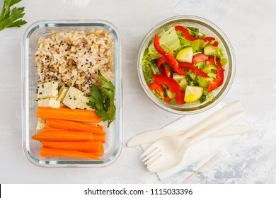 Healthy meal prep containers with brown rice, tofu and vegetable salad overhead shot with copy space. Healthy vegan food concept.
