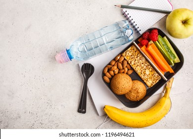 Healthy meal prep containers with cereal bar, fruits, vegetables and snacks. Takeaway food on white background, copy space, top view.
