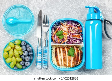 Healthy meal prep containers with  chicken and cole slaw. Container with berries. Bottle. Top view