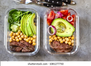 Healthy meal prep containers with chickpeas, goose meat , tomatoes, avocado, lemon and spinach. Top view