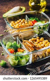 Healthy meal prep containers with chickpeas, chicken, tomatoes, cucumbers, avocados and broccoli. Top view