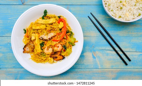 Healthy Meal Of Spicy Singapore Noodles With Egg Fried Rice, On A Wooden Blue Table Top, With No People