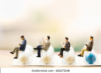 Healthy and medicine concept. miniature people : small businessman figures reading/posing on pills/capsules