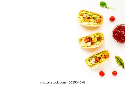 Healthy mexican tacos with vegetables, chicken fillet, tomato, tortillas, salad, corn on white background. Flat lay, top view