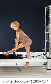 Healthy middle aged woman doing fitness stretching in the gym at tower reformer wearing dress and high hills