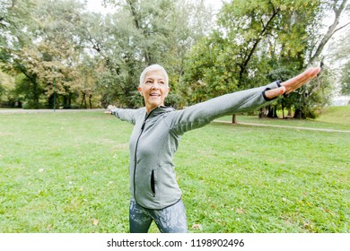 Healthy Middle Aged Woman In Sportswear Doing Stretching Exercise In The Park