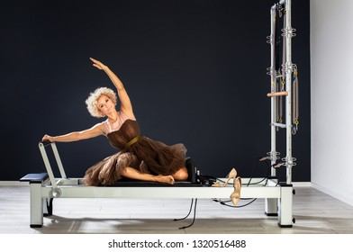 healthy middle aged woman stretching at gym wearing evening dress