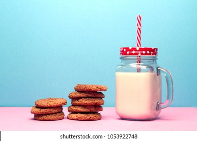 Healthy milk and cookies on the pink table and on the blue background