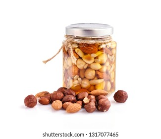 Healthy mix of natural honey with different nuts in a jar on white background