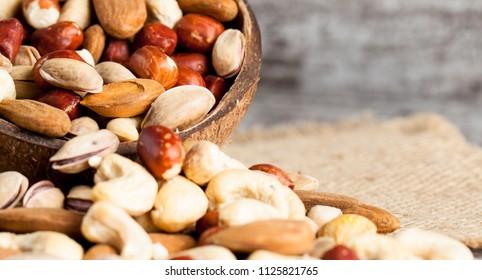 Healthy mix nuts on wooden background. Almonds, hazelnuts, cashews, peanuts, pistachios, brazilian nuts