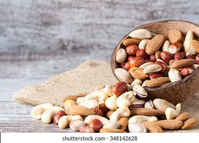 Healthy mix nuts on wooden background. Almonds, hazelnuts, cashews, peanuts, brazilian nuts