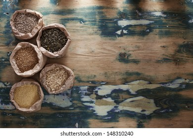 Healthy mix. Various types of beans, seeds, nuts and grains in paper bags on a rustic wooden table. Grain texture added.