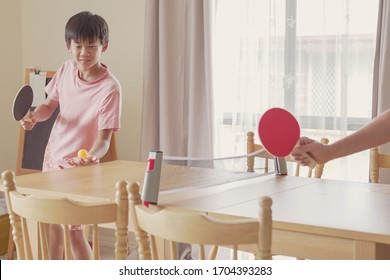 Healthy mixed Asian preteen boy playing table tennis on dining table at home, tween exercise, child fitness, family workout, stay healthy and fit during social distancing, lockdown, isolation concept
