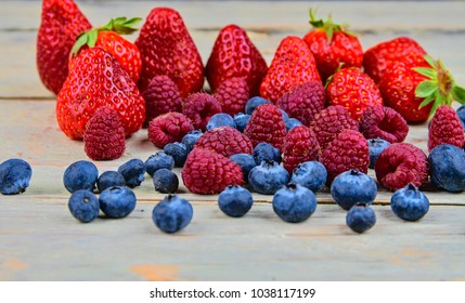 Healthy mixed fruit and ingredients with strawberry, raspberry, blueberry. Berries on rustic white wooden background. Close-up. Macro image.