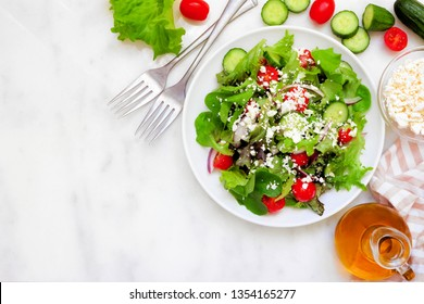 Healthy mixed salad with mixed greens, cucumber, onion, tomatoes and feta cheese. Above scene corner border against a white marble background with copy space.