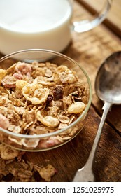 Healthy morning breakfast bowl full of organic granola with a spoon and a jug of milk on an old wooden table