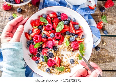 Healthy morning food, Breakfast oatmeal granola or muesli with various berry and milk, yogurt, wooden rustic background. Woman hands hold plate, sppon, flatlay top view