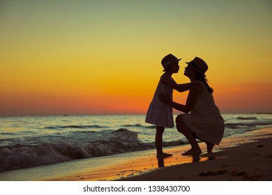 healthy mother and child tourists on the ocean shore at sunset kissing.