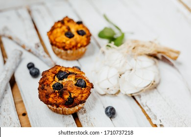 Healthy muffins with coconut flour and blueberries on light wooden plate decorated with mint an conch shells