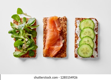 Healthy multigrain crackers with lamb's lettuce, salmon, cucumber and cottage cheese on a white background viewed from above. Top view