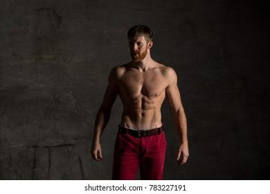 Healthy muscular bearded man on dark background