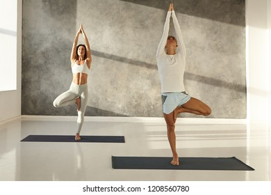 Healthy muscular young Caucasian man in shorts and fit slim woman in leggings standing barefooted on mats in spacious gym during morning yoga class, doing Vrksasana pose or Tree asana exercise