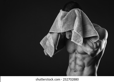 Healthy muscular young man after a workout on dark background.Fitness man holding a green towel against dark background.Strong Athletic Man Fitness Model Torso showing  abs. holding towel.