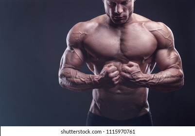 Healthy muscular young man against a dark background. Bodybuilder shows his body