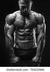 Healthy muscular young man. Bodybuilder shows his body. Black and white image