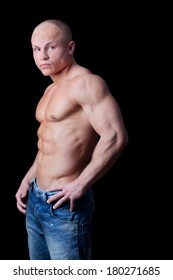 Healthy muscular young man on a black background