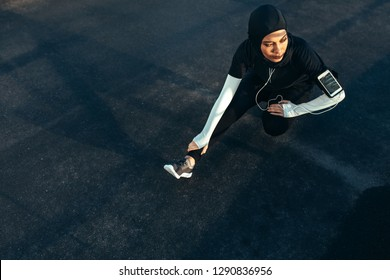 Healthy muslim woman with hijab doing exercise in morning. Hijab girl doing leg stretching workout on the street.