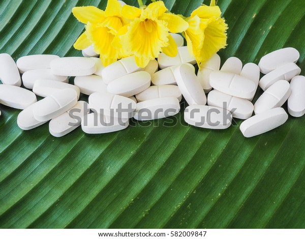 Healthy and Nature Concept: Calcium white tablet a good supplement for woman bone ,In a white bottle incline on banana leaf,