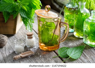 Healthy nettle tea, bottles of infusion, nettle plants and bottle of homeopathic globules on wooden table. Homeopathy and herbal medicine.