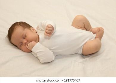 Healthy newborn baby sleeping on white sheet