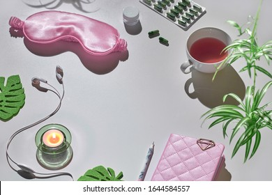 Healthy night sleep creative concept in pink and green. Sleep mask, earphones, tea, sleeping pills, diary notebook. Silver grey background with exotic leaves. Text space, copy-space, place for text.