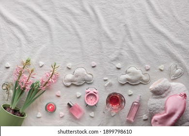 Healthy night sleep creative concept in pink and green. Off white, ivory textile background. Pink hyacinth flowers, alarm clock. Orthopedic pillow, sleep mask, tea, candle and warm bottle. Copy-space.