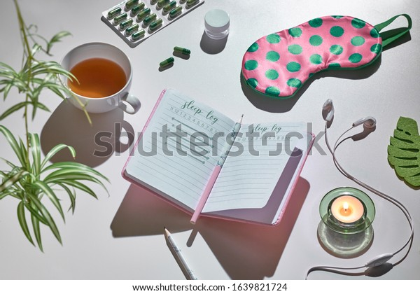 Healthy night sleep creative concept in pink and green. Sleep mask, earphones, tea, sleeping pills, diary notebook. Silver grey background with green house plant leaves, tinted image.