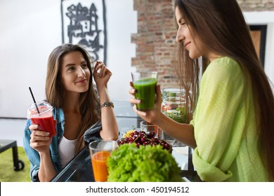 Healthy Nutrition. Beautiful Happy Women Drinking Fresh Juice, Vegetable Detox Smoothie Indoors. Fit Girls Enjoying Weight Loss Drinks Together At Home. Diet And Fitness Food Concept