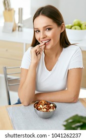 Healthy Nutrition. Beautiful Young Woman Eating Nuts