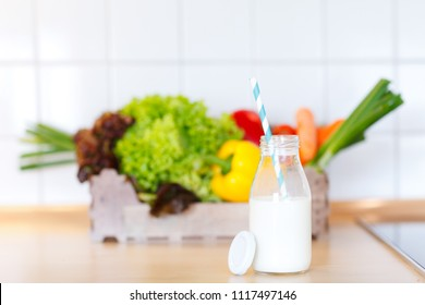 healthy nutrition with bottle of milk and a straw and a box filled with vegetables