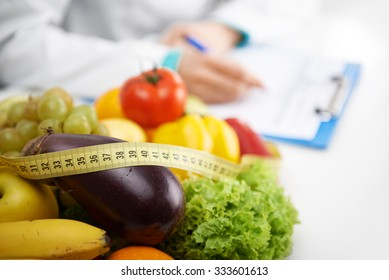 Healthy nutrition concept. Close-up of fresh vegetables and fruits with measuring tape lying on doctor's desk.  - Shutterstock ID 333601613