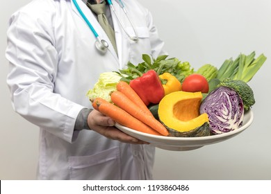 Healthy and nutrition concept. Doctor holding bowl of fresh fruits and vegetables.